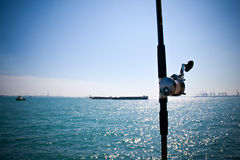 Fishing rod by the sea. A fishing rod in the foreground with the sea in the background royalty free stock image