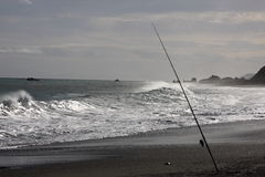 Fishing rod at sea shore. With waves breaking in the background Royalty Free Stock Photos