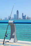 Fishing rod on the seafront against the backdrop. Of Abu Dhabi buildings royalty free illustration