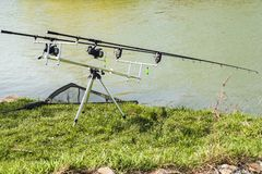 The fishing rod is set on the river bank. Good luck for fishing. royalty free stock images