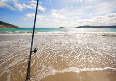 Fishing rod on a Spanish beach. Fixed fishing rod set up on a beach near the surf on the incoming tide.  Blue sky with clouds, turquiose sea Royalty Free Stock Photography