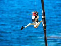 Fishing rod with a spinning reel. With sea beach ocean background Royalty Free Stock Image