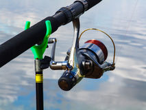 Fishing rod on the stand and coil with the fishing line closeup Royalty Free Stock Images