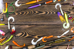 Fishing rod, tackles and fishing baits, reel on wooden board background.  Stock Photography