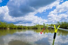 A fishing rod thrown into the water with a bright round indicator on the background of blue sky and green bushes. The concept of a
