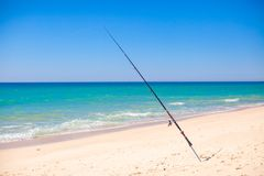 Fishing rod in white sand on tropical beach, Stock Photo
