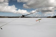 Fishing rod for winter fishing with a balancer. Fishing rod for winter fishing with a rocker lies on the ice of the lake stock photos