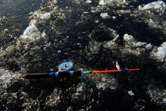 Fishing rod for winter fishing lies on the ice in winter stock photography
