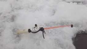 Fishing rod for winter fishing near ice hole stock video footage