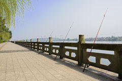Fishing rods against riverside stone balustrade in sunny spring Royalty Free Stock Image