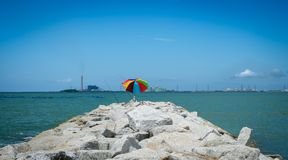Fishing rods and colourful umbrella on rock coast Royalty Free Stock Photos