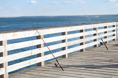 Fishing Rods lined up along a pier Stock Photo