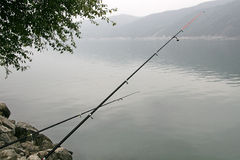 Fishing rods over the water. Fishing rods on riverside over the water stock photo