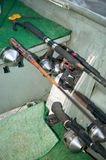 Fishing rods, reels and angling equipment in boat. A close up of freshwater fishing rods, reels and angling equipment on the deck of an aluminium dinghy Royalty Free Stock Image