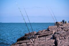 Fishing rods and reels on jetty in Port Aransas, TX at the Gulf of Mexico