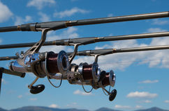 Fishing rods with reels on a support system rod pod and tourist tent the holiday camp on the bank. stock photography