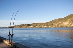 Fishing rods by the river Ebro. Sunny view of two rods by the river Ebro, Spain. Fishing scenery royalty free stock photography