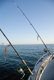 Fishing rods at sea. Two fishing rods attached to a boat's railing, seascape Stock Images