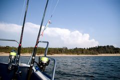 Fishing rods at sea. Two fishing rods attached to a boat's railing, seascape. A beach on the horizon. SEA FISHING COLLECTION royalty free stock photography