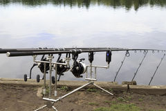 Fishing rods on tripods. Three fishing rods attached to bite alarms set on the side of a river Royalty Free Stock Photos