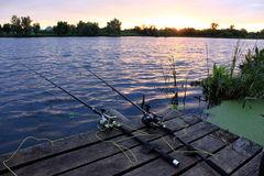 Fishing rods on the wooden bridge at sunset Stock Images
