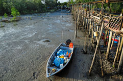 Fishing sampan stranded near to wooden pier Stock Images