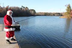 Fishing Santa. Santa on a dock fishing in a nature setting royalty free stock image