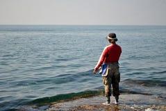 Fishing at Sea. Man fishes at open sea side Royalty Free Stock Image