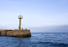 Fishing in sea. Some fishermen fishing from the tip of a jetty with a port entrance beacon Royalty Free Stock Photos