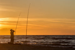Fishing on the sea. Anglers fish the sea at sunset Stock Image
