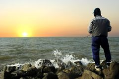 Fishing in the sea by enjoying the beautiful sunrise scenery. With the bright sunlight that so brightly starts the activity of the fishermen excitedly, in the royalty free stock images