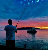 Fishing at sea at sunset Royalty Free Stock Photos