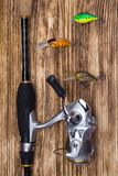 Fishing set on a wooden background: collected spinning and bait in the form of multi-colored small fish stock photos