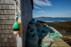 Fishing shack,Nova Scotia. A picturesque,wide angle view of old fishing shack,ropes and buoys  in coastal village on the Bay of Fundy,Brier Island,Nova Scotia Royalty Free Stock Image