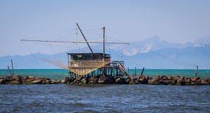 Fishing shack to trawl the estuary, with mountains behind Royalty Free Stock Photos