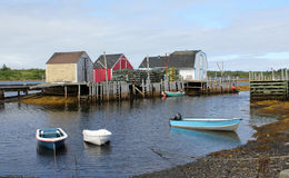 Fishing village, Nova Scotia. A picturesque landscape of colorful fishing shacks ,lobster traps and boats in quiet cove at Blue Rocks,Nova Scotia Royalty Free Stock Images