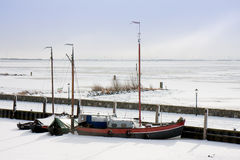 Fishing ship enclosed by ice in harbor Royalty Free Stock Photos
