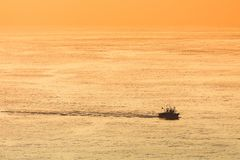 Fishing ship. At sunset on sea stock image