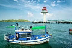 Fishing ship in sea and white light house Stock Photo