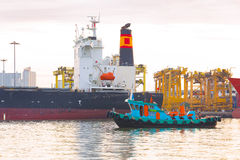Fishing ships beside container cargo freight ship in the morning Royalty Free Stock Photo