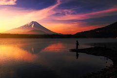 Fishing at Shoji lake with Mt. Fuji. Silhouette scenic view of a man fishing at Shoji lake with mt. Fuji view reflection during sunrise with twilight sky at dawn Stock Image