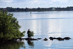 Fishing on shoreline rocks 3. A man fishing from a rock jetty along the shoreline royalty free stock images