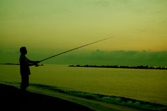 Fishing Silhouette. Man fishing at beach in silhouette Stock Photo