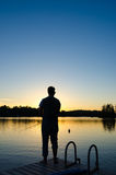 Fishing Silhouette. Fishing as the sun is setting on a lake Royalty Free Stock Photos