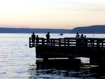 Fishing Silhouettes. Families fishing on a public pier at the Tacoma waterfront, silhouetted against an evening sky Royalty Free Stock Photography