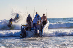 Fishing Ski-Boats Waves. Fishing surf Ski-boats crew and rods hits a small wave at first light royalty free stock photography