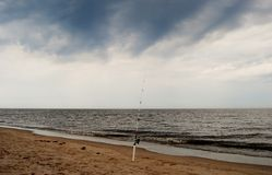 Fishing rod on a beach. Fishing rod on a sandy beach with sea in the background under dark clouds Royalty Free Stock Images
