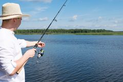 Fishing in the summer in sunny weather on a beautiful lake. Fishing in the summer in  sunny weather on a beautiful lake royalty free stock photo