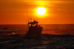 Fishing Sunrise. Fishing boat going out into ocean at sunrise Stock Photo