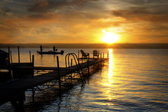 Fishing Sunrise. A beautiful autumn sunrise on the pebbled shores of Lake Cayuga in the Finger lakes region of New York state. A pier leads out to a deck with Royalty Free Stock Photography